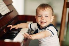 Il piccolo ragazzo felice gioca il piano Fotografie Stock Libere da Diritti