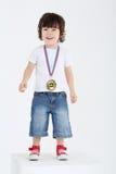 Il piccolo ragazzo felice in scarpe da tennis rosse sta sul grande cubo bianco Fotografia Stock