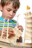 Il piccolo ragazzo lavora con zelo sulla nave artificiale Fotografia Stock