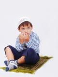 Il piccolo ragazzo musulmano sta pregando Fotografia Stock