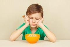 Il piccolo ragazzo scontento non vuole mangiare il porridge fotografia stock