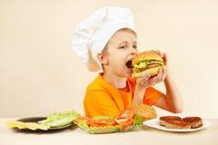Il piccolo ragazzo sorridente in cappello dei cuochi unici sta assaggiando l'hamburger cucinato Immagini Stock