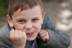 Il piccolo ragazzo sorridente minaccia per i pugni che prendono lo scaffale di pugilato Fotografie Stock Libere da Diritti