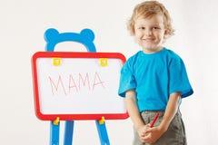 Il piccolo ragazzo sorridente sveglio ha scritto il mama di parola Fotografia Stock