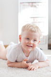 Il ragazzino sveglio sta trovandosi sul tappeto bianco Fotografie Stock