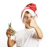 Il piccolo ragazzo sveglio in cappello rosso di Santa isolato con l'americano dei contanti fa Fotografia Stock Libera da Diritti