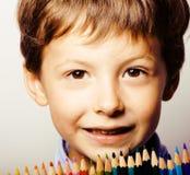 Il piccolo ragazzo sveglio con le matite di colore si chiude sul sorridere, l'istruzione f fotografia stock libera da diritti