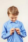 Il piccolo ragazzo sveglio ha fissato i bottoni sulla camicia luminosa Immagine Stock Libera da Diritti