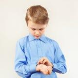 Il piccolo ragazzo sveglio ha fissato i bottoni sulla camicia luminosa della manica Fotografia Stock