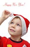 Il piccolo ragazzo sveglio porta il cappello della Santa Immagine Stock