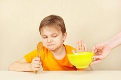 Il piccolo ragazzo sveglio rifiuta di mangiare il porridge Fotografia Stock