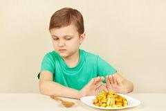 Il piccolo ragazzo sveglio rifiuta di mangiare le fritture Fotografia Stock