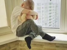Il piccolo ragazzo triste si siede il problema di espressione infelice su una finestra con un orsacchiotto solo Fotografia Stock Libera da Diritti