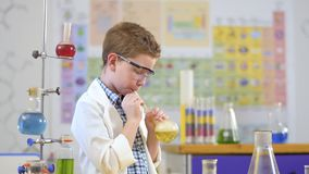 Il piccolo scienziato sveglio fa l'esperimento del laboratorio con liquido archivi video