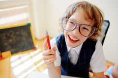 Il piccolo scolaro divertente in vetri si siede ad uno scrittorio della scuola Immagine Stock Libera da Diritti