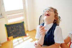 Il piccolo scolaro divertente in vetri si siede ad uno scrittorio della scuola Immagine Stock