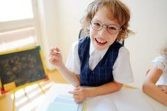 Il piccolo scolaro divertente in vetri si siede ad uno scrittorio della scuola Fotografia Stock