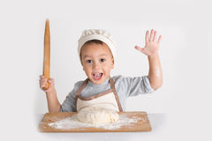Il piccolo specialista culinario con la pasta ed il matterello immagini stock