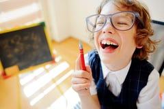 Il piccolo studente allegro occhialuto si siede allo scrittorio della scuola Immagini Stock