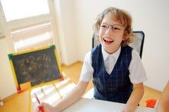 Il piccolo studente allegro occhialuto si siede allo scrittorio della scuola Fotografie Stock Libere da Diritti