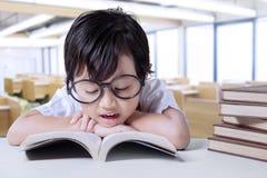 Il piccolo studente gode dei libri colti nella classe Fotografie Stock Libere da Diritti