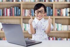 Il piccolo studente soddisfatto mostra i pollici su in biblioteca Fotografia Stock Libera da Diritti