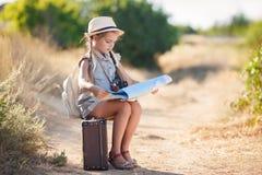 Il piccolo viaggiatore studia la mappa mentre si siede sulla vecchia valigia Immagine Stock