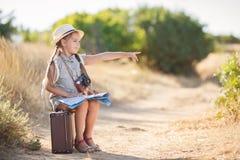 Il piccolo viaggiatore studia la mappa mentre si siede sulla vecchia valigia Immagini Stock Libere da Diritti