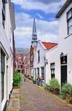 Il piccolo vicolo con bianco ha intonacato le case e una chiesa sui precedenti, il gouda, Paesi Bassi Immagini Stock