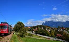 Il piccolo villaggio ed il treno rosso in alpi Fotografia Stock