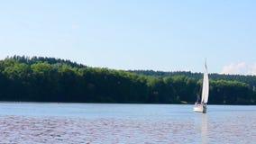 Il piccolo yacht sul grande lago sta navigando più vicino alla macchina fotografica archivi video