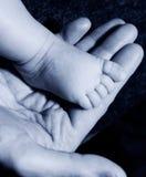 Il piede del bambino sopra equipaggia la mano Immagini Stock