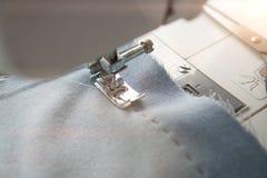Il piede del presser della macchina per cucire preme il tessuto blu Macchina per cucire e oggetto di abbigliamento blu L'ago dell immagine stock libera da diritti