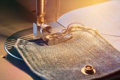 Il piede della macchina per cucire sul tessuto dei jeans ha tonificato, luce calda immagine stock libera da diritti