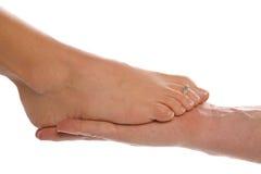 Il piede di Womans sopra equipaggia la mano Fotografia Stock