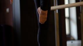 Il piede nudo del ballerino funziona lungo la gamba sul pavimento alla sbarra di balletto archivi video