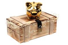 Il piggybank dorato sul caso di legno ha chiuso con padloc Fotografia Stock