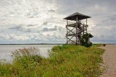 Il pilastro con il percorso di camminata e l'allerta di legno si elevano nel lago un giorno nuvoloso, Lettonia di liepaja Fotografia Stock