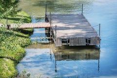 Il pilastro di legno è riflesso nell'acqua calma Immagini Stock