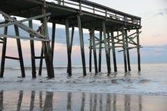 Il pilastro di pesca della spiaggia tesse sopra le onde ed il litorale sabbioso fotografia stock