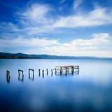 Il pilastro o il molo di legno rimane su un lago blu. Esposizione lunga. immagine stock libera da diritti