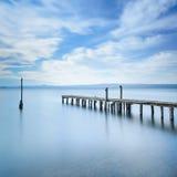 Il pilastro o il molo di legno rimane su un lago blu. Esposizione lunga. fotografia stock libera da diritti