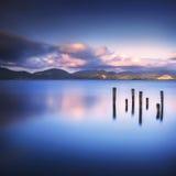 Il pilastro o il molo di legno rimane su un refle blu del tramonto e del cielo del lago Immagini Stock Libere da Diritti