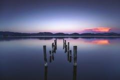 Il pilastro o il molo di legno rimane su un refle blu del tramonto e del cielo del lago Immagine Stock
