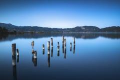 Il pilastro o il molo di legno rimane su un refle blu del tramonto e del cielo del lago Immagini Stock