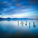 Il pilastro o il molo di legno rimane su una riflessione blu del tramonto e del cielo del lago sull'acqua. Versilia Toscana, Itali Fotografia Stock Libera da Diritti