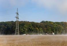 Il pilone dell'elettricità è l'accumulazione al campo Immagine Stock Libera da Diritti
