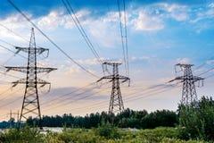 Il pilone elettrico nel giacimento del riso con il cielo blu Concetto di distribuzione di energia fotografie stock