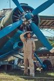 Il pilota bello coraggioso in un ingranaggio pieno di volo che sta vicino ad un retro aeroplano militare e distoglie lo sguardo immagini stock