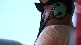Il pilota dell'elicottero mette sopra la cuffia avricolare per i negoziati con lo spedizioniere Richiede il permesso di decollo video d archivio